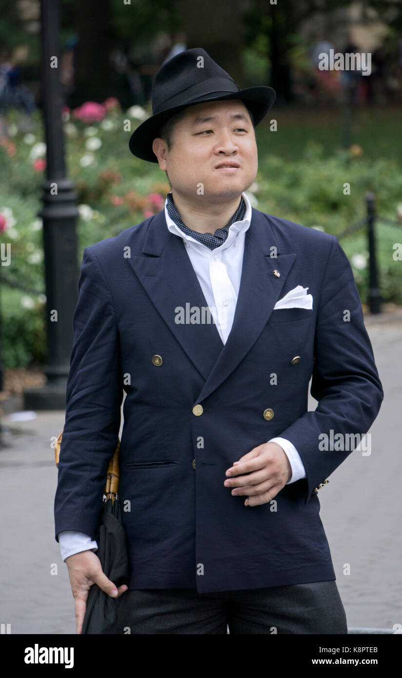 A very dapper Asian man with a top hat, ascot, sport jacket and pocket hankie in Washington Square Park in Greewich - Stock Image