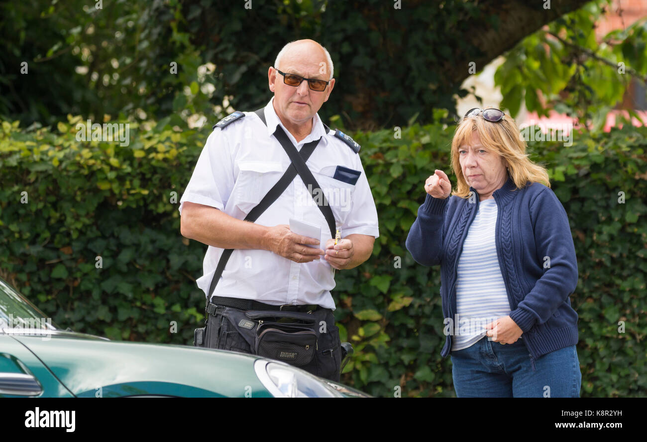 Parking warden writing out a parking ticket in the UK. Note: The lady shown is NOT the one receiving the ticket. - Stock Image