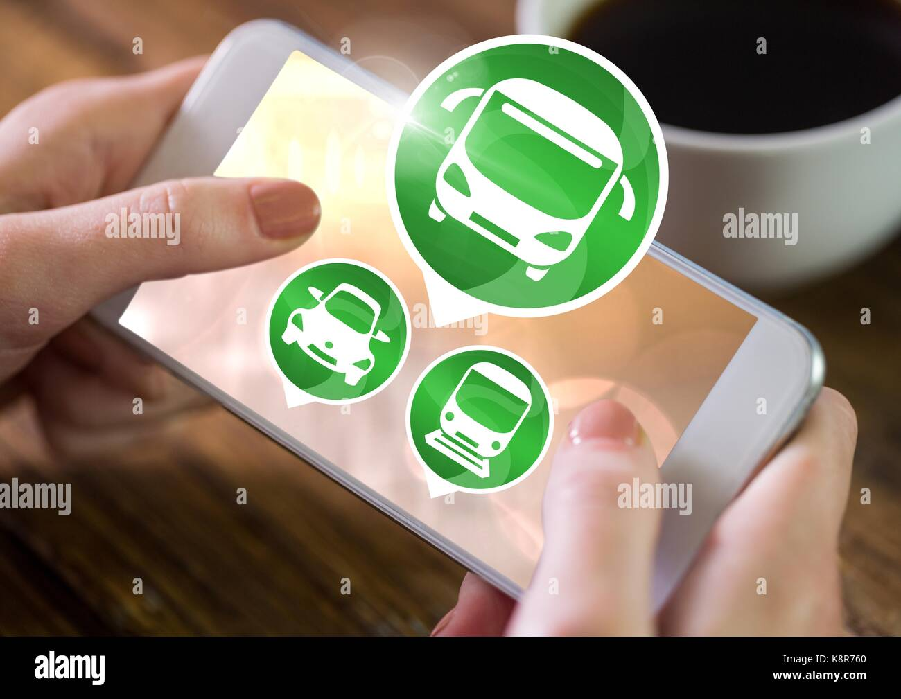 Digital composite of Hand holding phone with transport icons at table - Stock Image