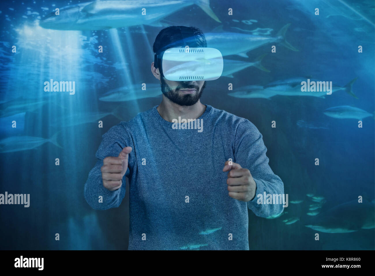 Man driving with VR  against fish swimming with shark in darkest water - Stock Image