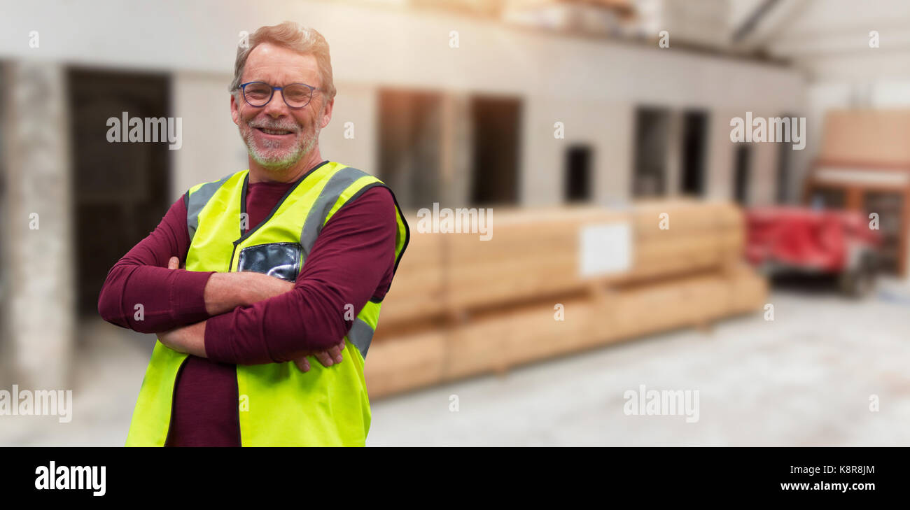 Confident senior worker with arms crossed wearing reflective clothing against workshop - Stock Image
