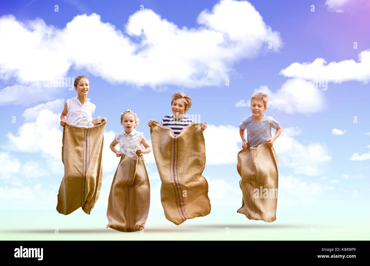 Friends playing sack race against blue sky - Stock Image