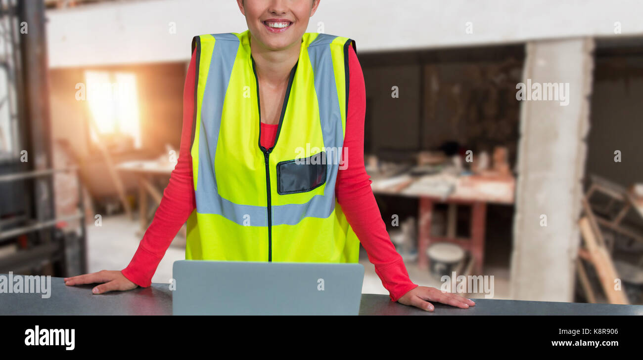 Portrait of confident female architect wearing reflective clothing against workshop - Stock Image