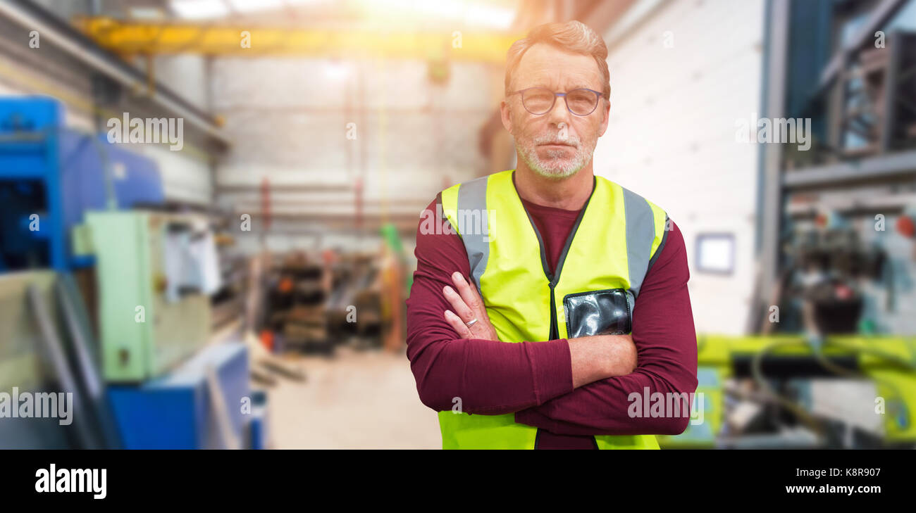 Portrait of senior worker wit arms crossed wearing reflective clothing against workshop - Stock Image