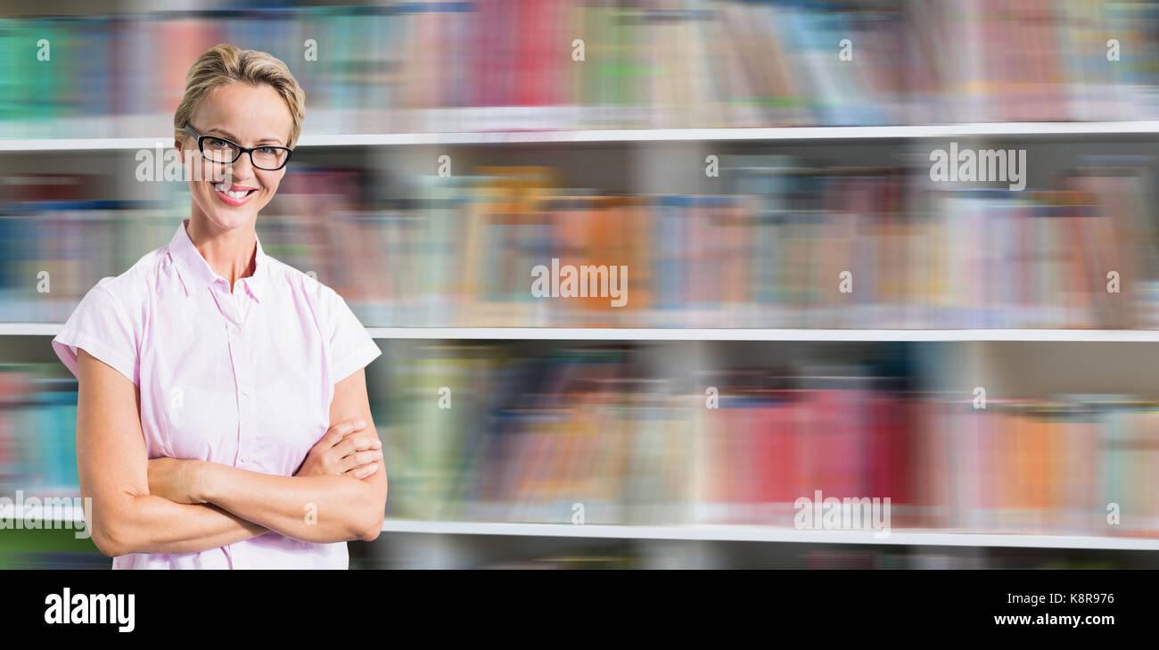 Portrait of smiling teacher against shelf of books Stock Photo