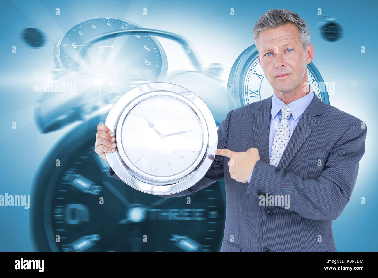 Portrait of businessman pointing at wall clock against graphic image of alarm and wall clocks - Stock Image