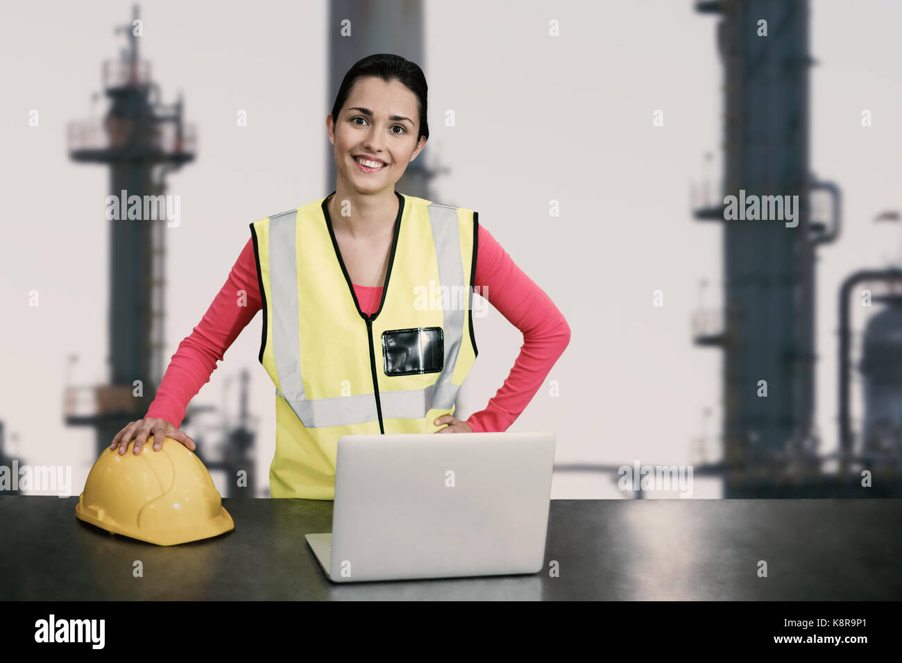 Portrait of female architect wearing reflective clothing against exterior of factory - Stock Image