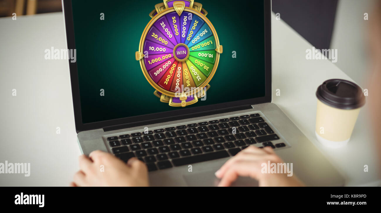 Graphic image of wheel of fortune on mobile screen against cropped hands of woman using laptop - Stock Image