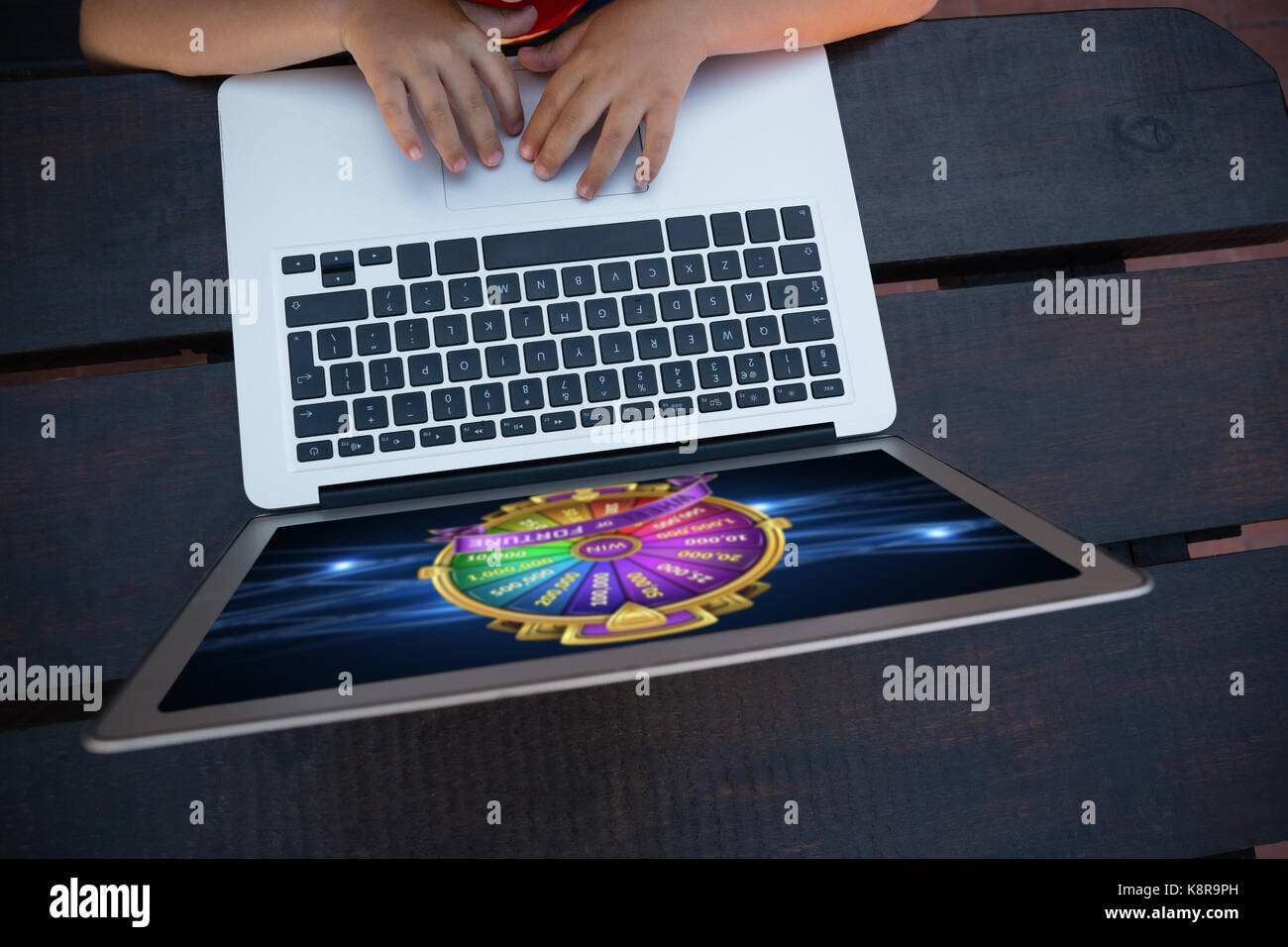 Wheel of fortune on mobile screen against overhead view of boy using digital laptop while sitting at table - Stock Image