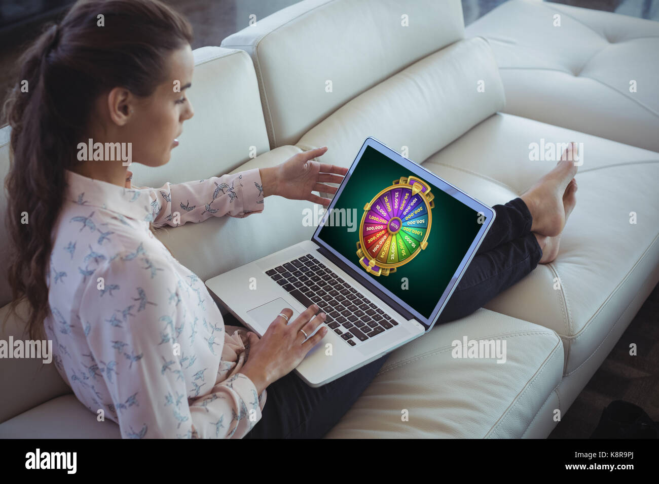 Graphic image of wheel of fortune on mobile screen against businesswoman using laptop while resting on sofa - Stock Image
