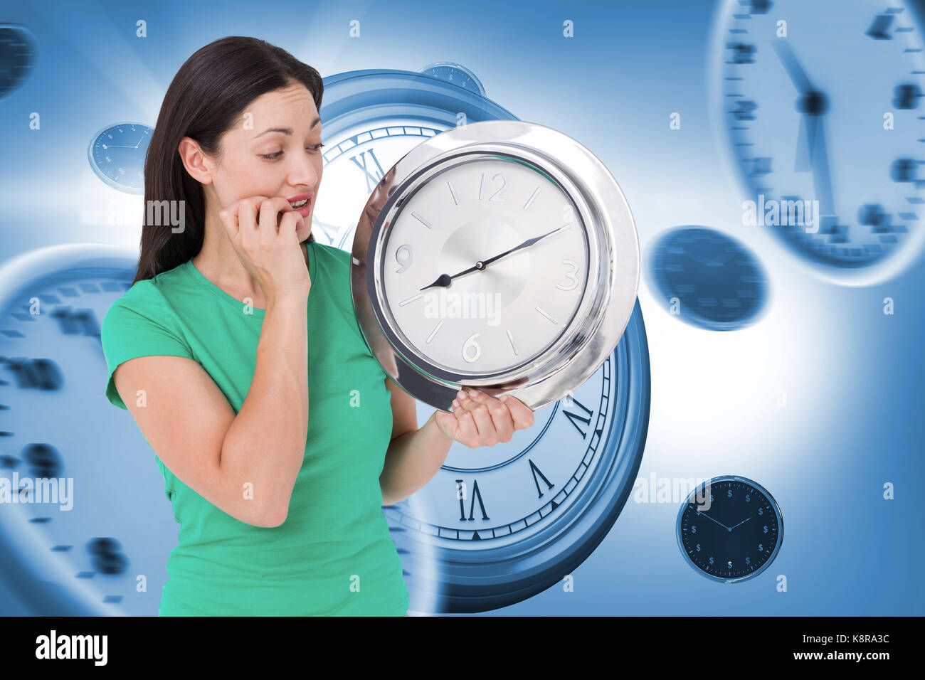 Brunette looking at wall clock against graphic image of wall clocks - Stock Image