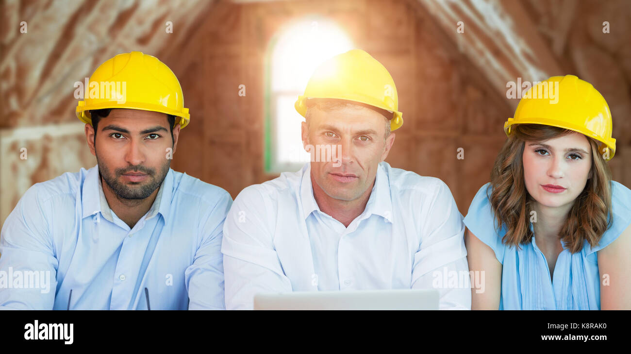 Portrait of architects wearing hardhats while sitting at table against room in house under construction - Stock Image