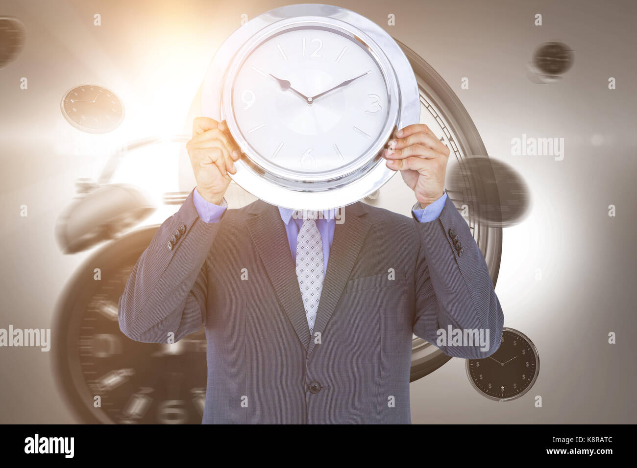 Businessman holding wall clock in front of face against digital image of alarm and wall clocks - Stock Image