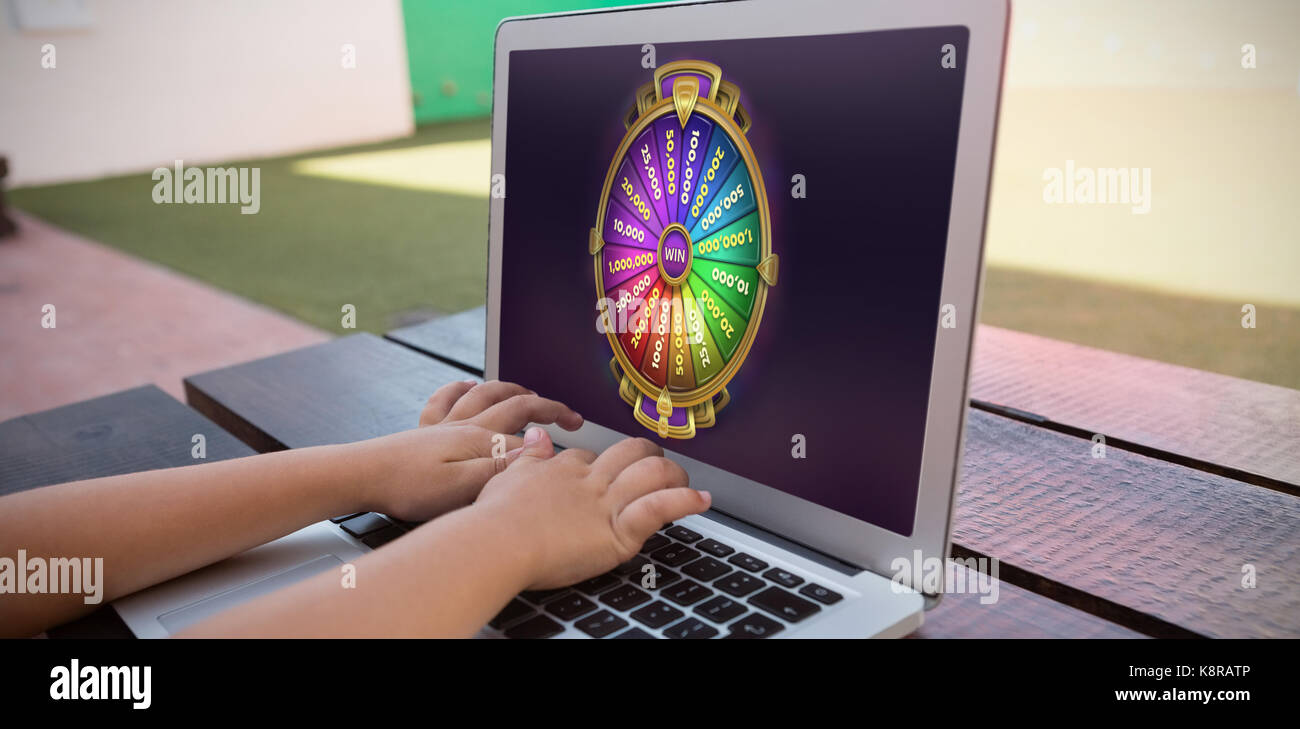 Colorful wheel of fortune on mobile screen against close up of boy using digital laptop while sitting at table - Stock Image