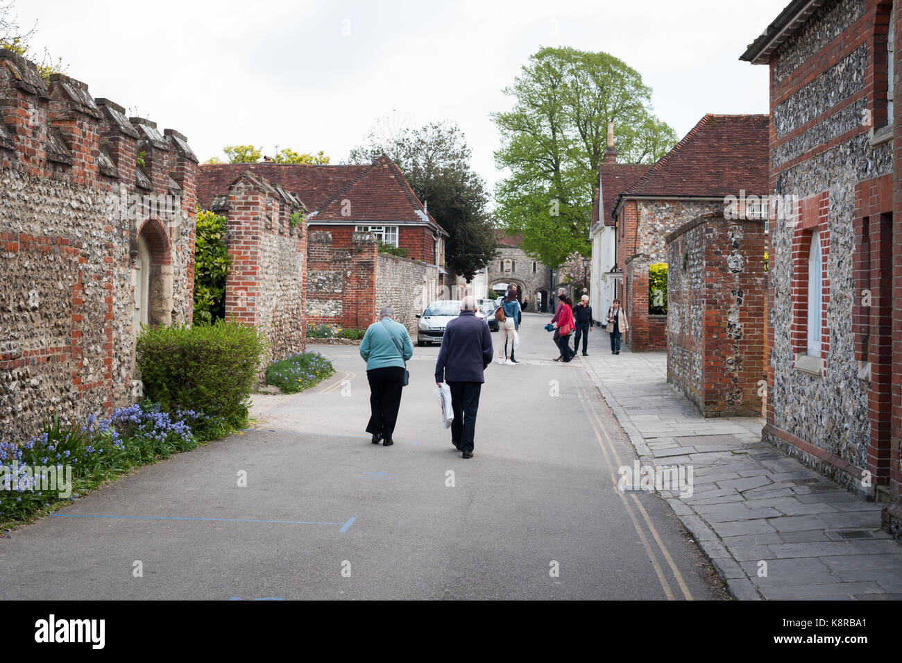 People walk down a road and past red brick buildings in Chichester, West Sussex, England. Stock Photo