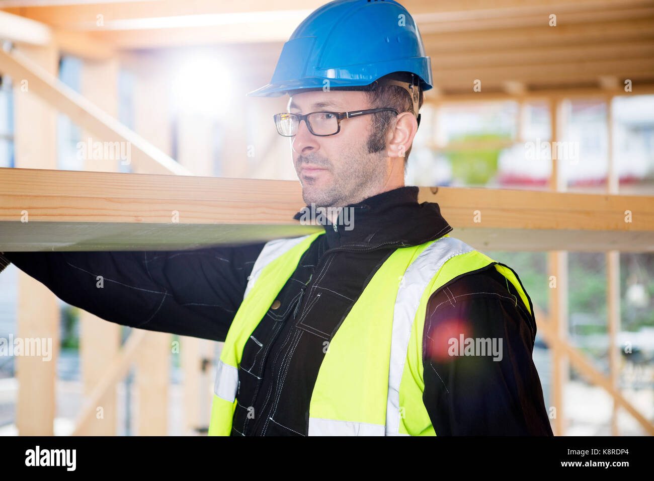 Carpenter In Protective Wear Carrying Wood On Shoulder Stock Photo