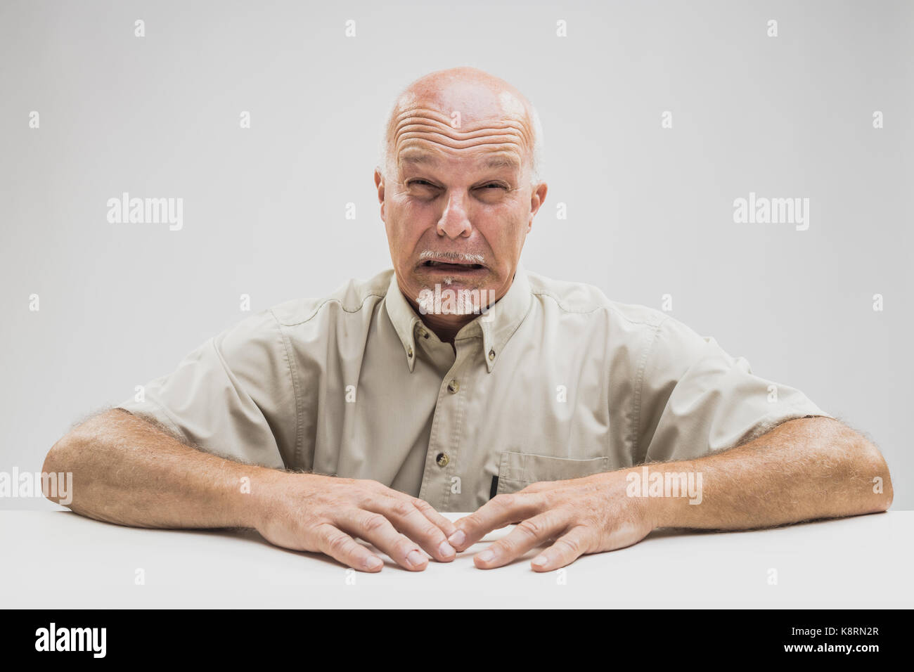 Emotional tearful elderly man blubbering with his face contorted into a grimace as he sits at a table over white - Stock Image