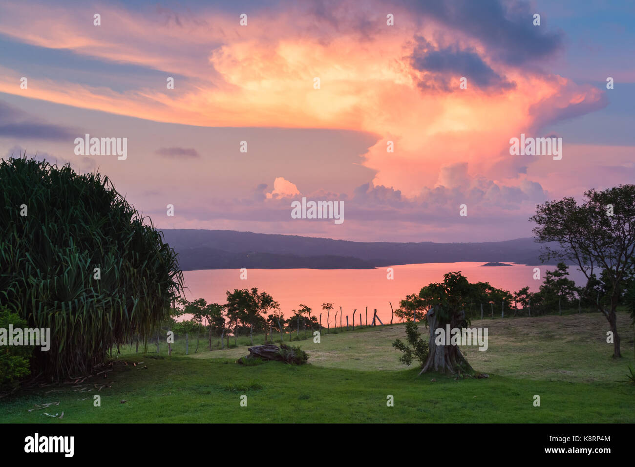 towering cloud reaching up towards the sky reflecting on Lake Arenal at the end of the day - Stock Image