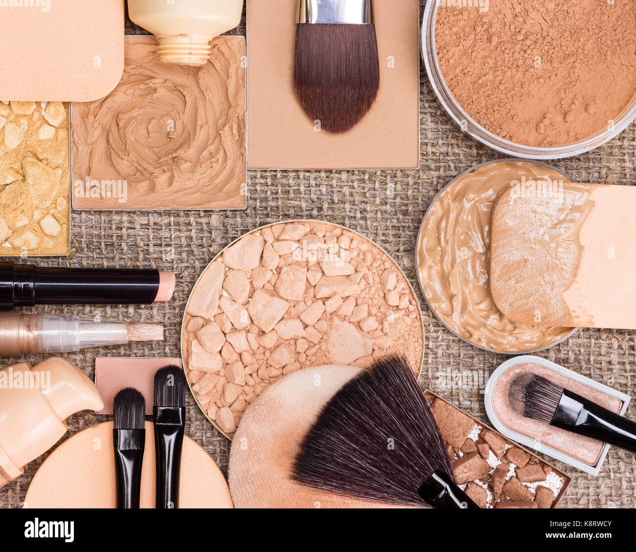 Makeup products to create the perfect complexion. Foundation, compact, loose and shimmer golden powder, crushed - Stock Image