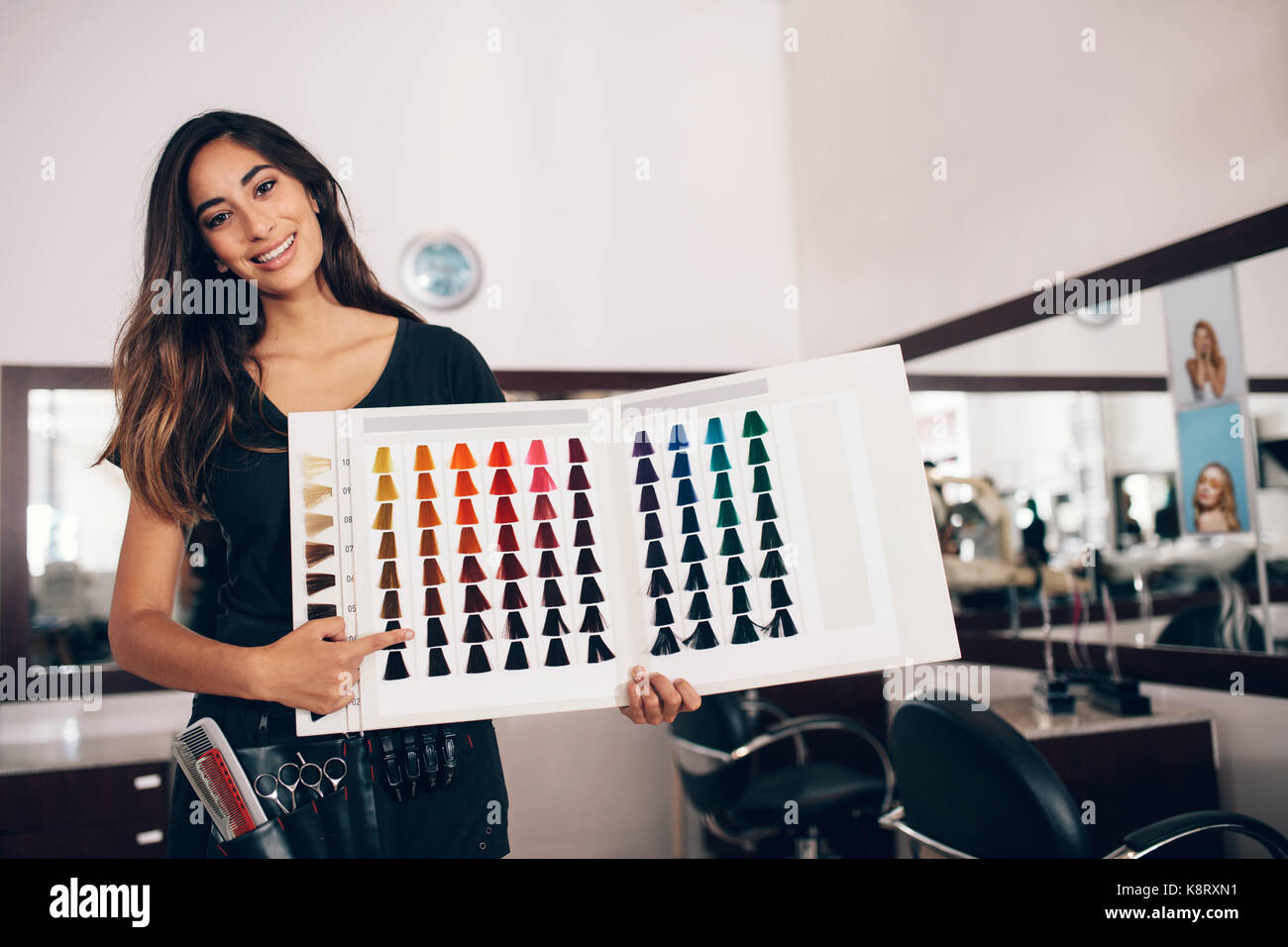 Professional woman hairdresser pointing at the hair color sample chart.  Woman with hairdressing accessories tied - Stock Image