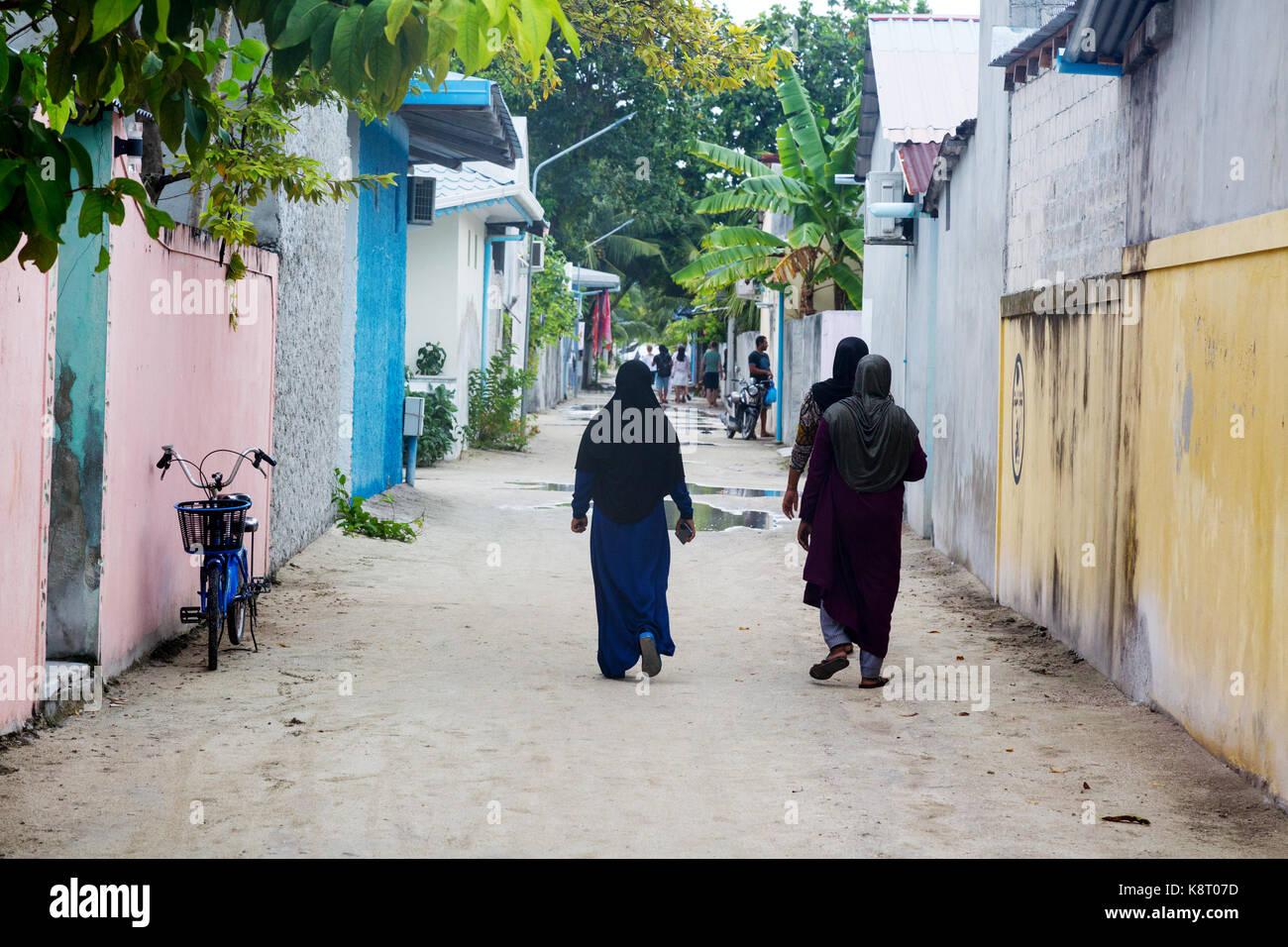 Local muslim women walking in the village, Rasdhoo island, the Maldives, Asia - Stock Image