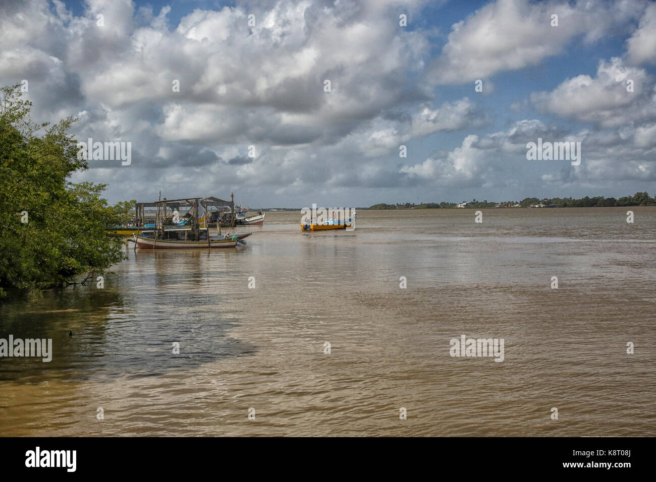 Suriname river with boats near the shore - Stock Image