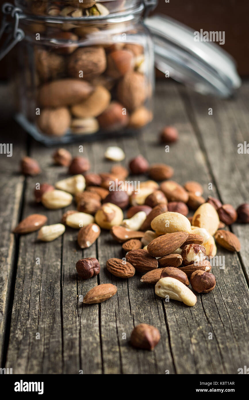 Different types of nuts. Hazelnuts, walnuts, almonds, brazil nuts and pistachio nuts on old wooden table. Stock Photo