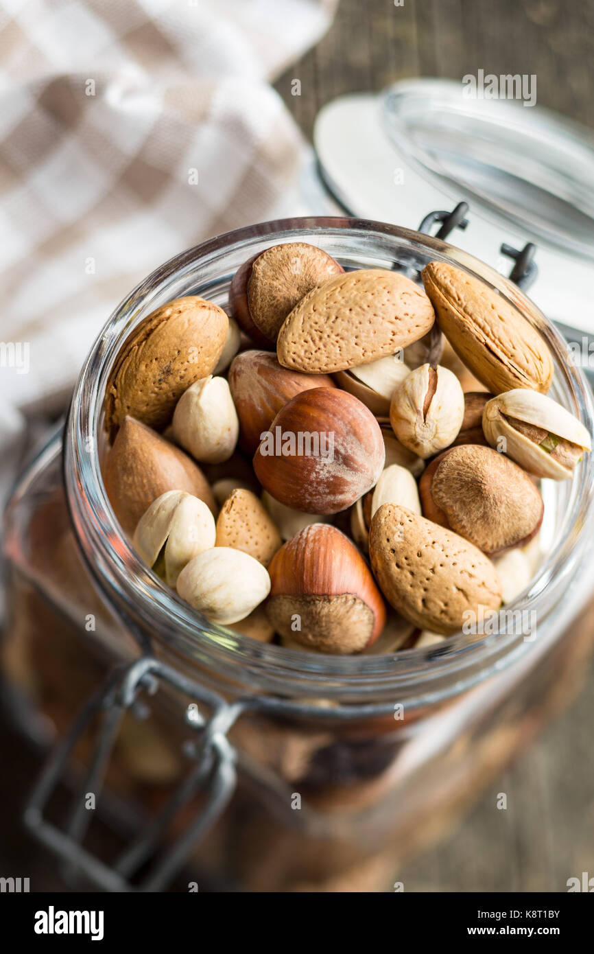 Different types of nuts in the nutshell. Hazelnuts, walnuts, almonds, pecan nuts and pistachio nuts in jar. - Stock Image