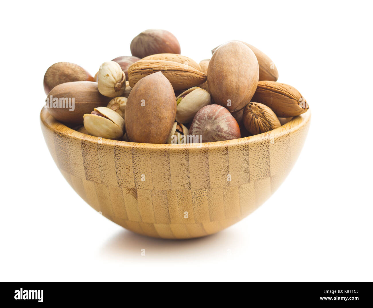 Different types of nuts in the nutshell. Hazelnuts, walnuts, almonds, pecan nuts and pistachio nuts in wooden bowl. - Stock Image