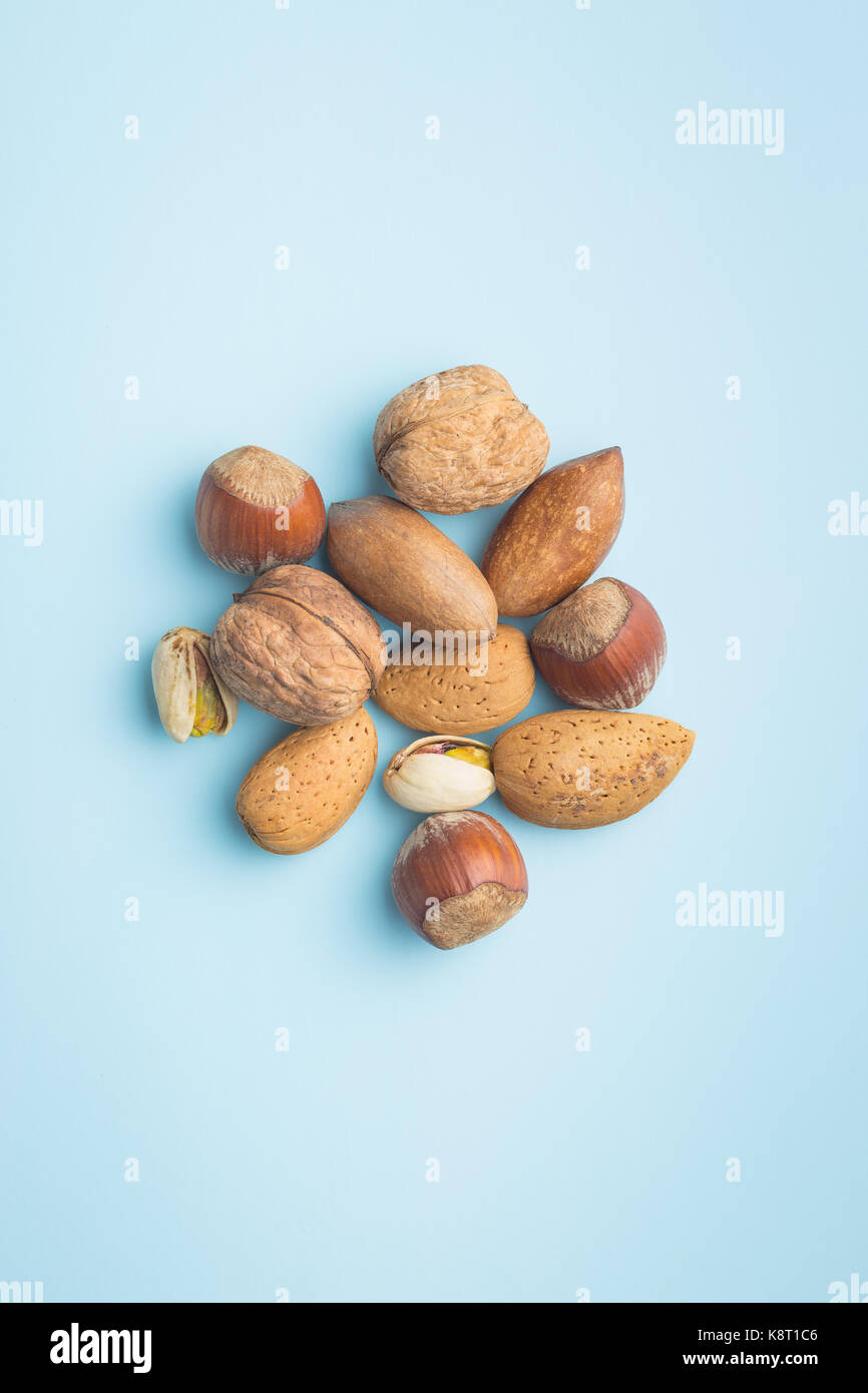 Different types of nuts in the nutshell on blue background. Dried nuts. - Stock Image