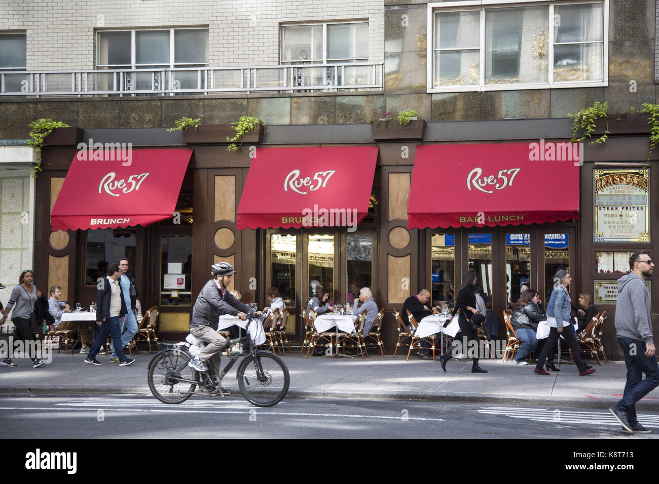 People have brunch on the sidewalk as pedestrians pass by at Rue 57 on 57th Street and Sixth Avenue in midtown Manhattan, - Stock Image