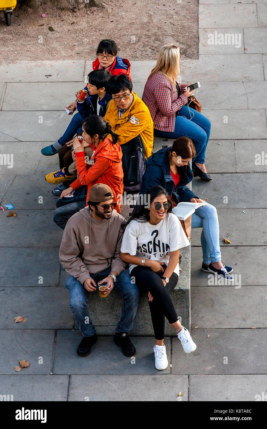 A Group Of Tourists Sitting On A Bench, The Southbank, London, UK - Stock Image