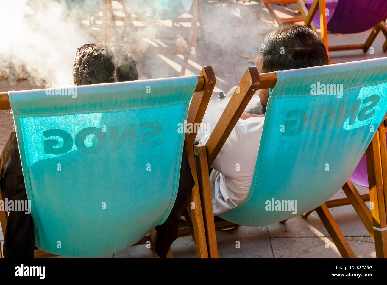 Two People Relaxing On The South Bank, London, UK - Stock Image