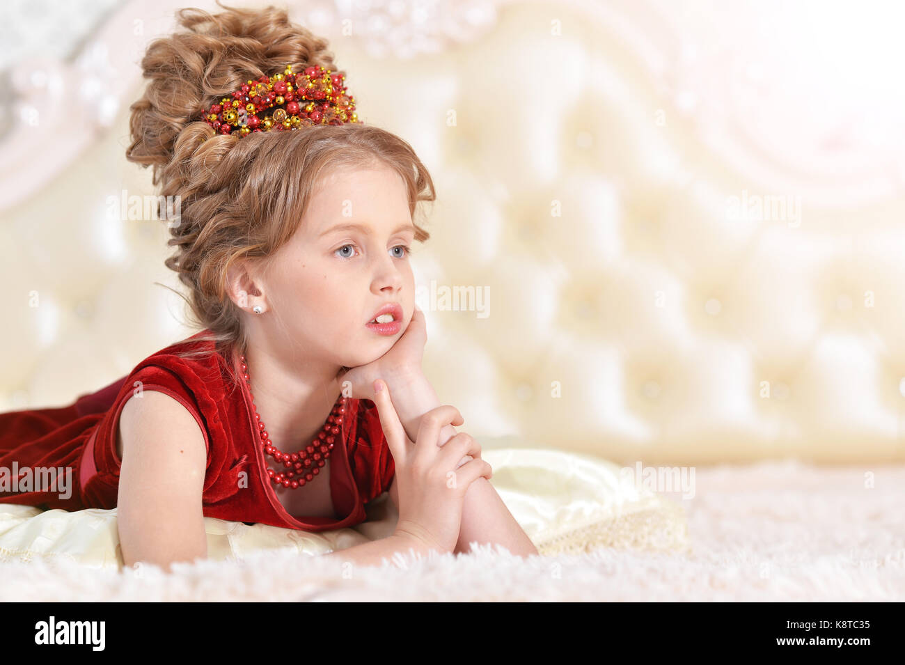 3674f78874d9 Cute little girl in red velvet dress with retro hairstyle lying on beige  couch