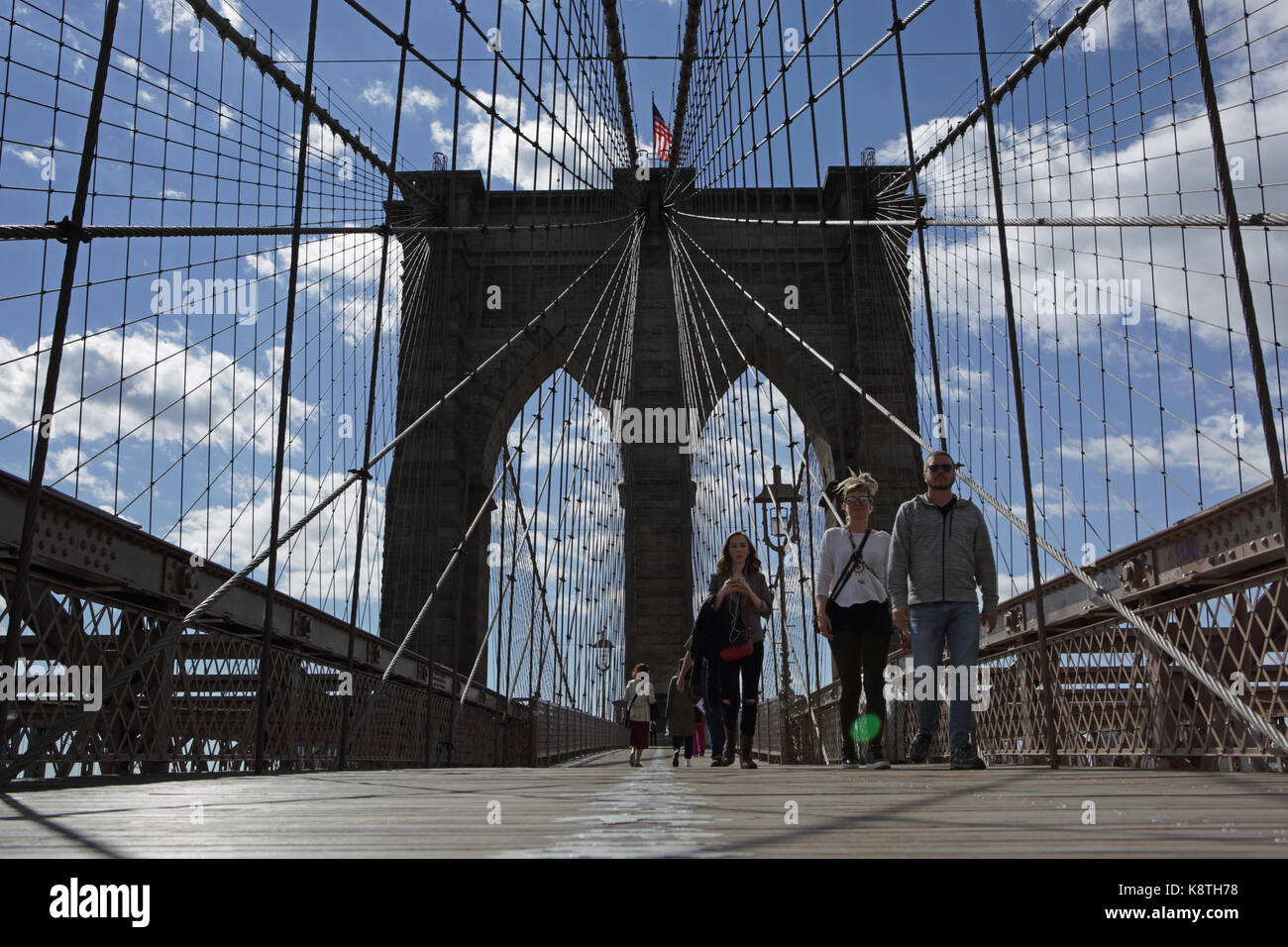 New York, NY, USA - May 3, 2017: Worms eye view of people walking to Manhattan across the Brooklyn Bridge on a sunny - Stock Image