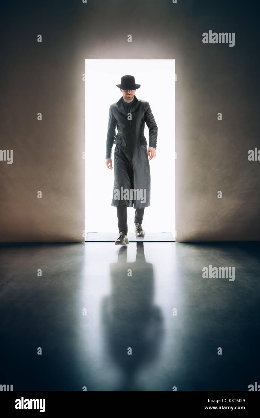 Man silhouette coming from the light of opening door in dark room. mystery concept - Stock Image