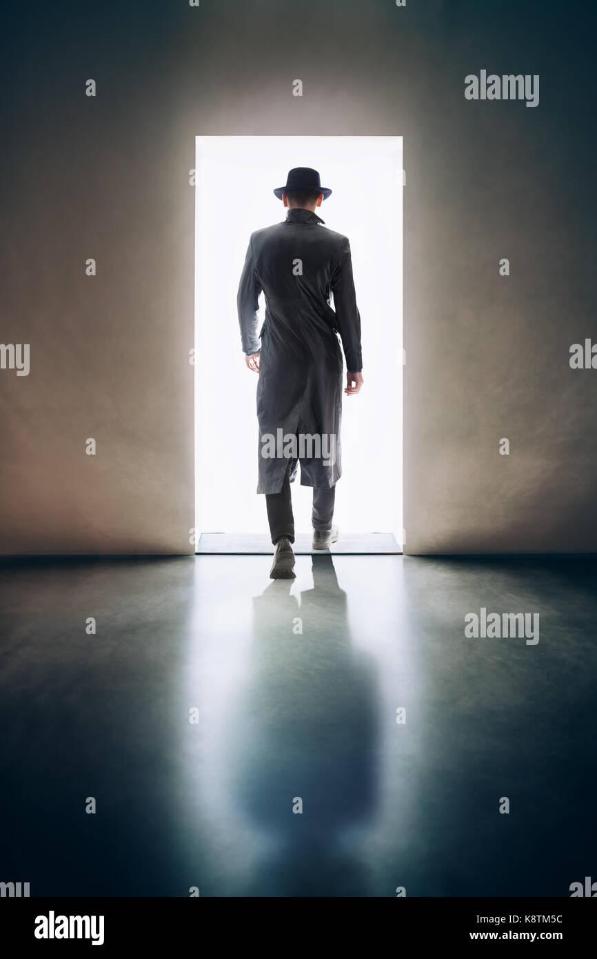 Man silhouette walking away in the light of opening door in dark room. escape concept - Stock Image
