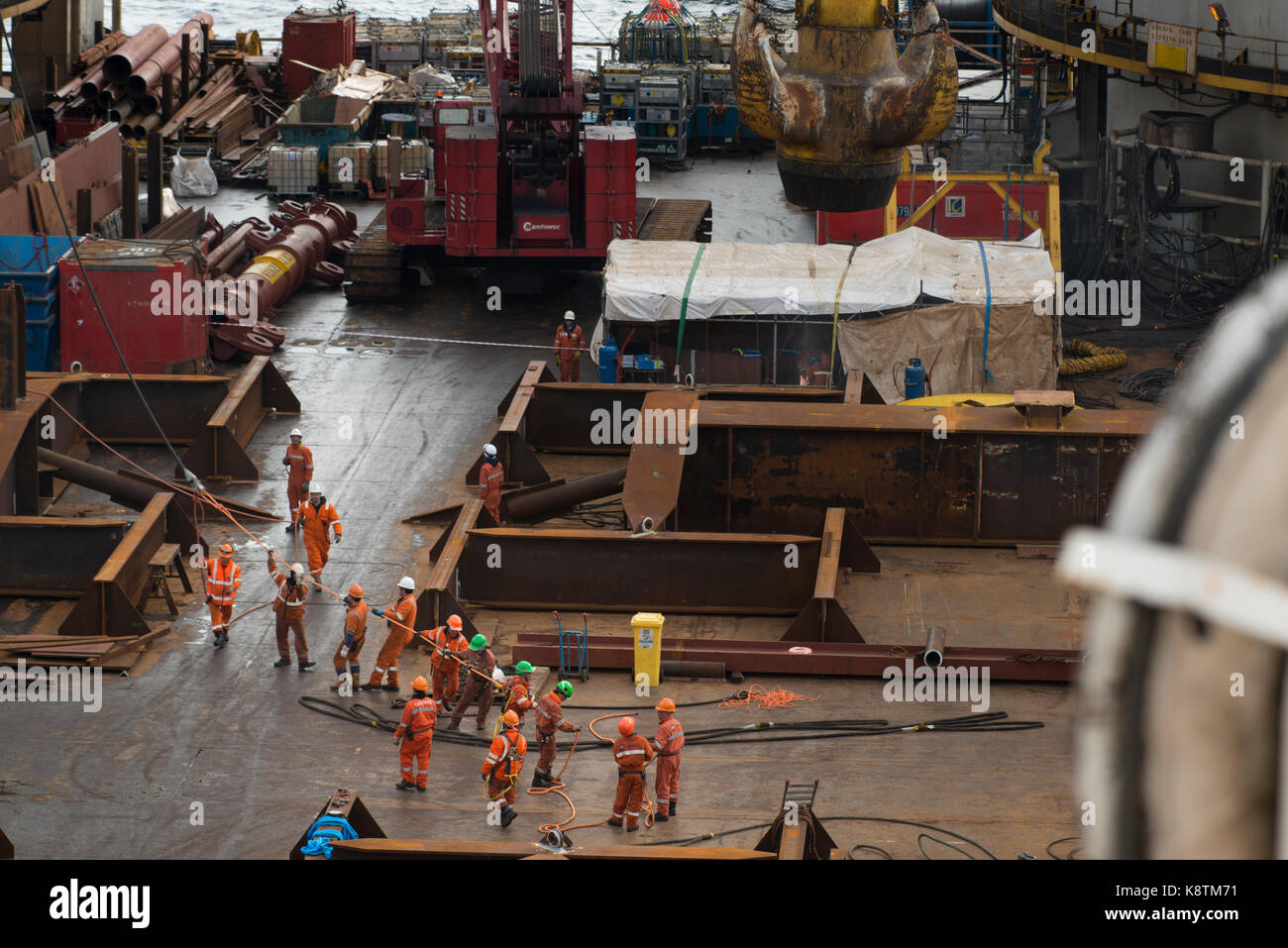 Workers on the deck of the Saipem S7000 heavy lifting vessel, pulling a rope. credit: LEE RAMSDEN / ALAMY - Stock Image