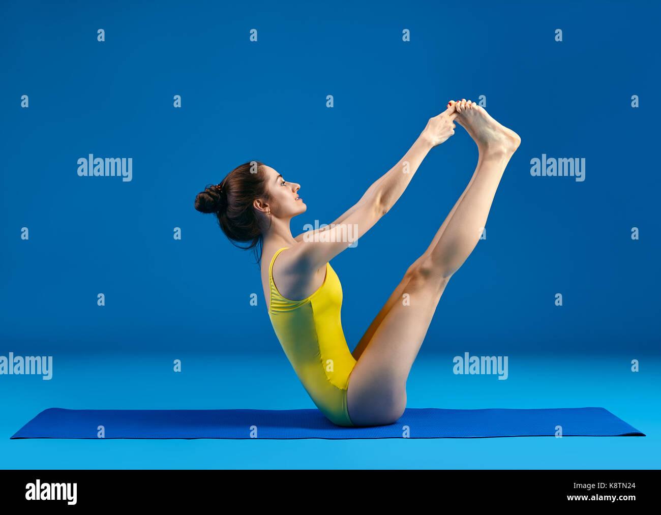 Young woman doing yoga asana both big toes pose. Ubhaya Padangusthasana - Stock Image