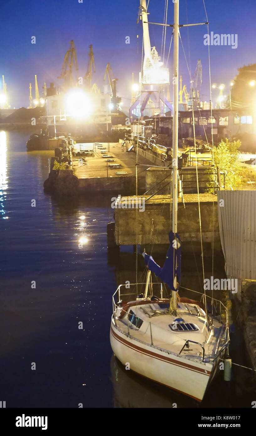 the yacht is berthed at the port at night in kaliningrad - Stock Image