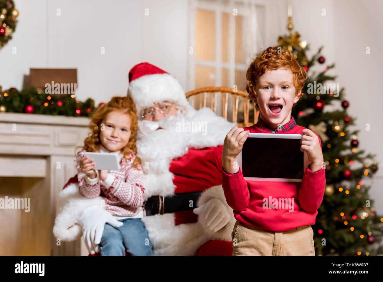 santa claus and children with digital devices - Stock Image