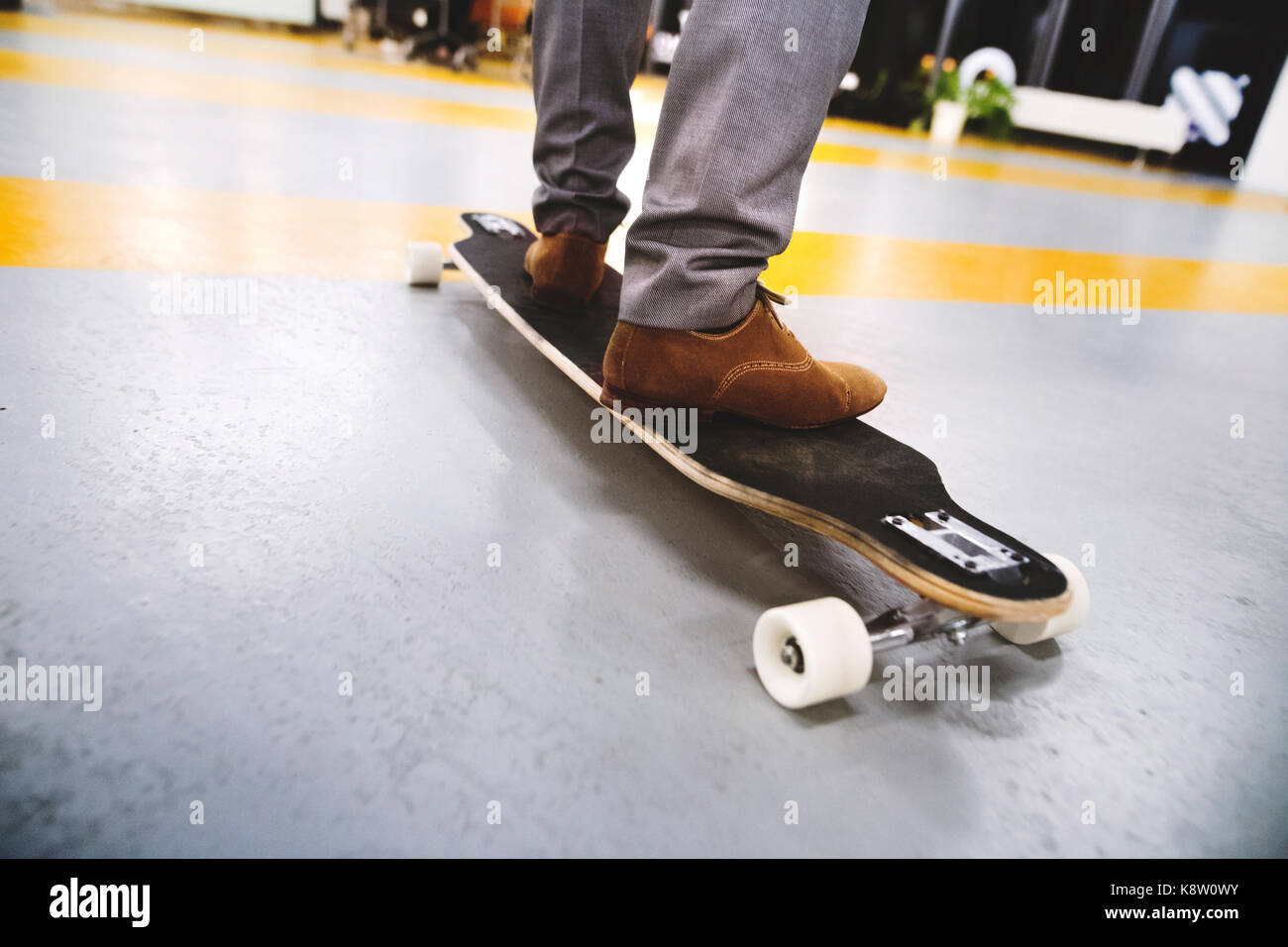 Unrecognizable businessman standing on longboard. - Stock Image
