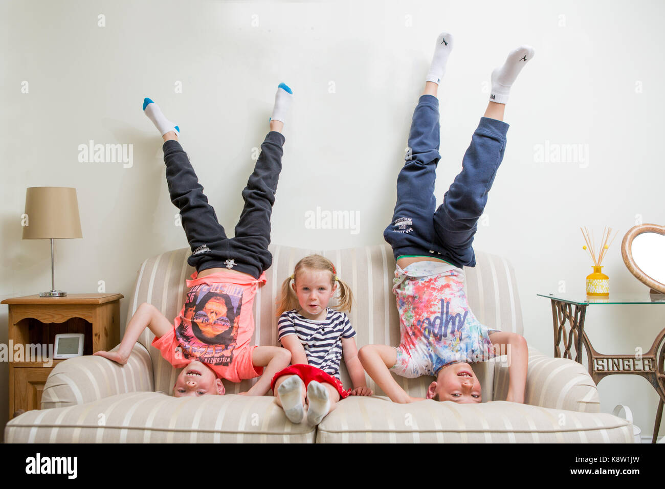 kids doing headstand on the sofa - Stock Image