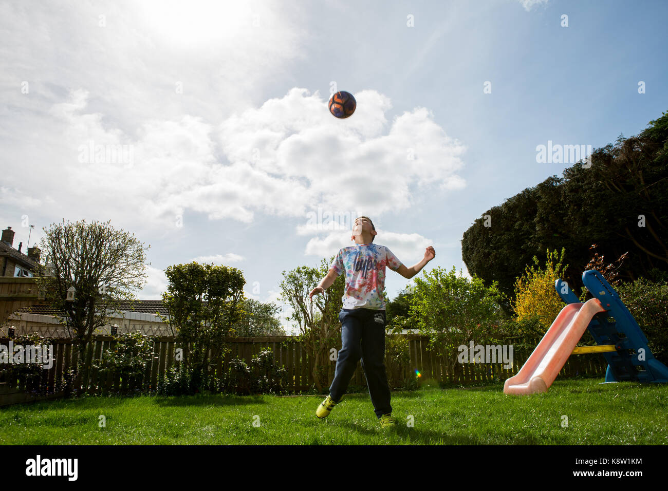 Boy playing football at home - Stock Image