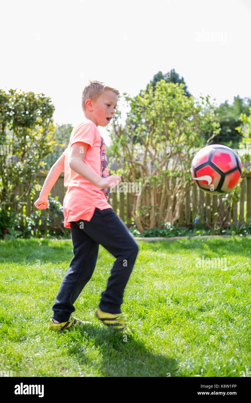 young boys playing football - Stock Image