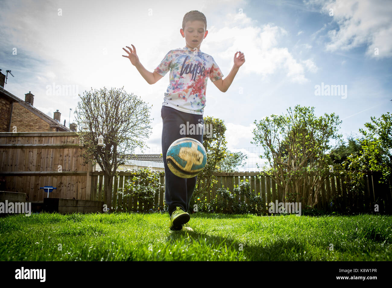 young boys playing football - Stock Image