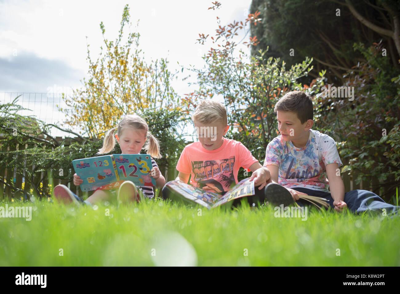 children reading in the garden - Stock Image