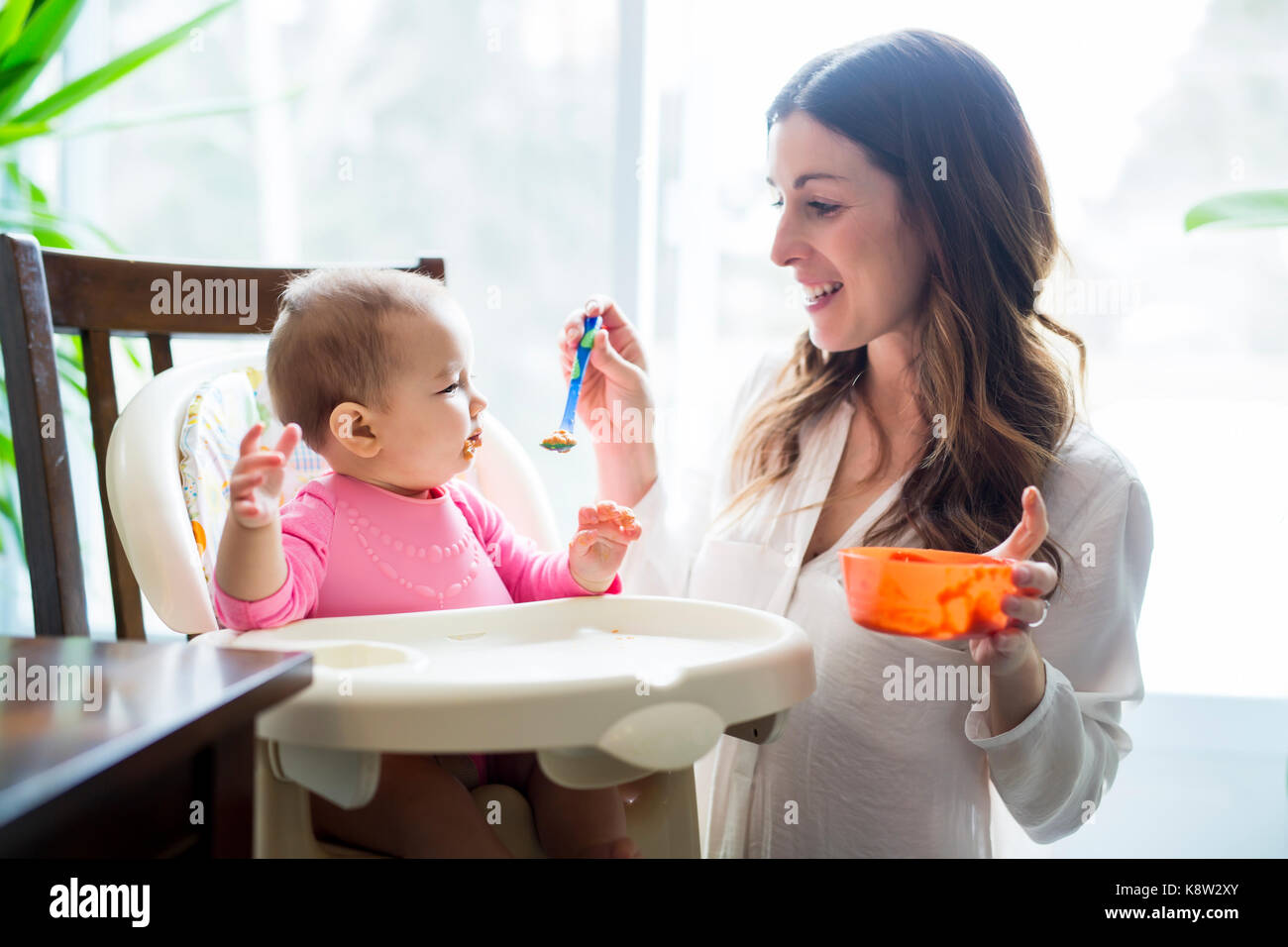 Mother feeding baby with spoon - Stock Image