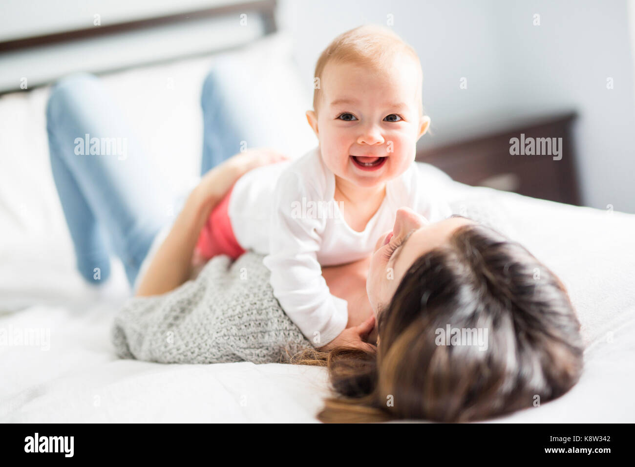 Mother and baby child on a white bed. - Stock Image