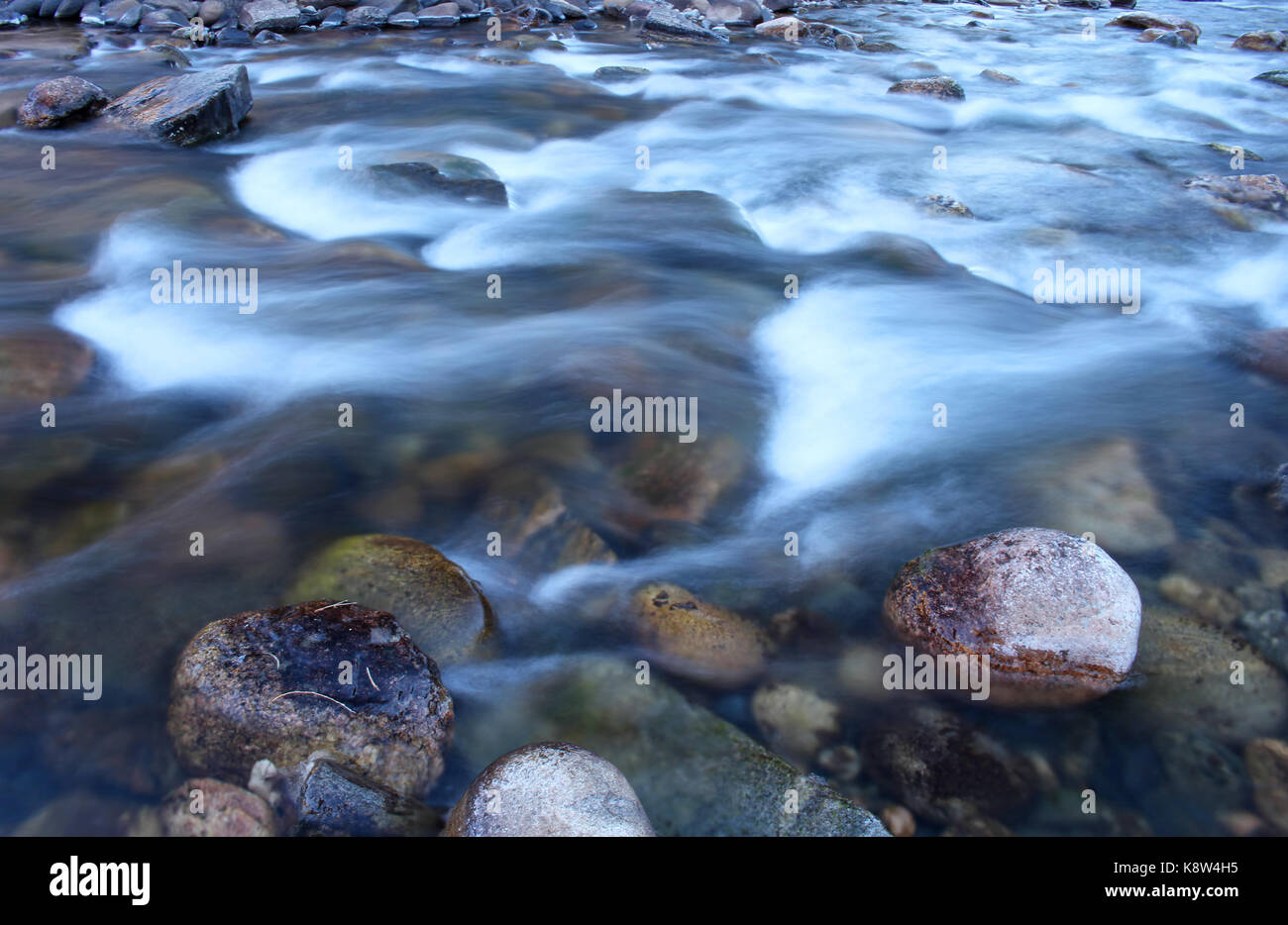 Icy water flowing swiftly down the Poudre River in Colorado. - Stock Image